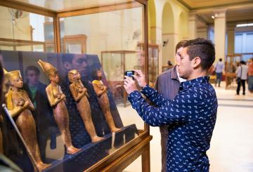 a tourist taking a photo inside the egyptian museum